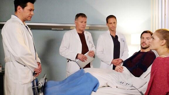 Ein Patient liegt im Bett und eine Gruppe Ärzte steht beratend um ihn herum.
