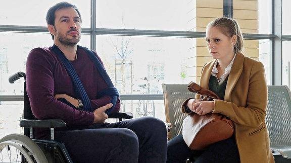 Ein Mann sitzt mit einem Arm in der Schlinge im Rollstuhl. Eine Frau sitzt neben ihm.