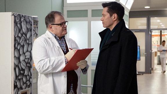 Dr. Philipp Brentano (Thomas Koch, re.) bringt einen Patienten in die Sachsenklinik und bietet Hans-Peter Brenner (Michael Trischan, li.) seine Unterstützung an. Als Hans-Peter dankend ablehnt, erklärt Philipp ihm die Schwierigkeiten mit dem cholerischen Patienten.