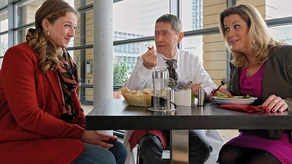 Dr. Kaminski (Udo Schenk, mi.), Sarah Marquardt (Alexa Maria Surholt, re.) und Wanda Schäfer (Henriette Nagel, li.) sitzen gemeinsam in der Cafeteria.