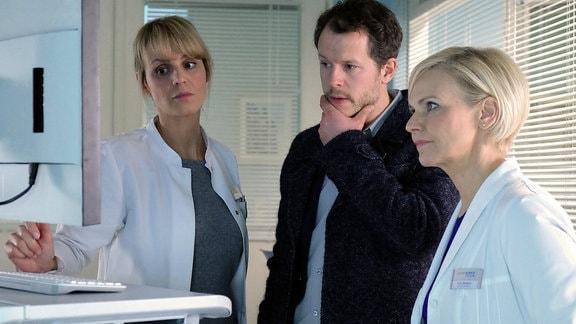 Tom Wolter (Mirko Lang, mi.) , Dr. Kathrin Globisch (Andrea Kathrin Loewig, re.) und Dr. Lea Peters (Anja Nejarri, li.) blicken besorgt auf einen Monitor.