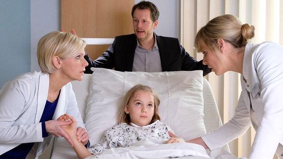 Dr. Lea Peters (Anja Nejarri, re.) und Dr. Kathrin Globisch (Andrea Kathrin Loewig, li.) und Tom Wolters (Mirko Lang, mi., oben) stehen besorgt am Bett von Toms Tochter.