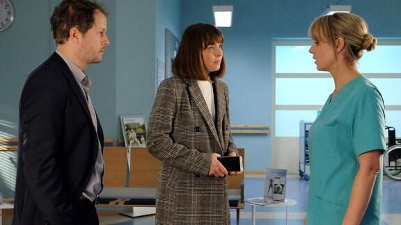 Dr. Lea Peters spricht  mit den aufgeregten Eltern Tom und Sina Wolter.