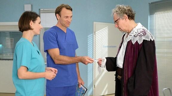 Ein Mann in Verkleidung spricht mit Dr. Stein und Dr. Weber