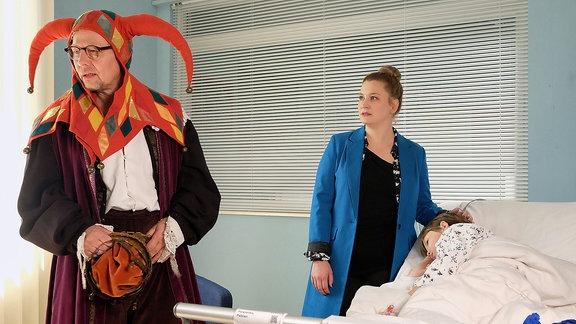 Ein verkleideter Mann und eine junge Frau im Krankenzimmer eines Jungen.