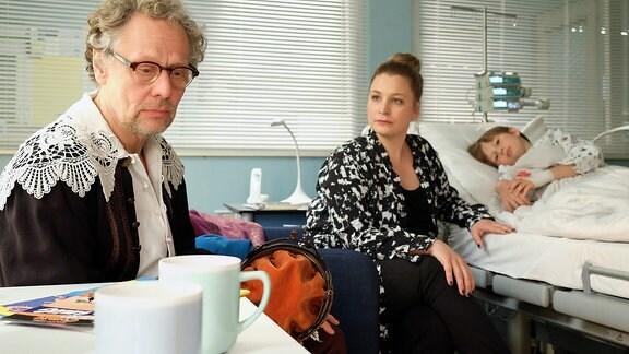 Ein älterer Mann und eine junge Frau im Krankenzimmer eines Jungen.