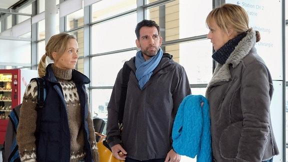 Dr. Lea Peters (Anja Nejarri, re.) wird zu Arbeitsbeginn von ihrem ehemaligen Patienten Lutz Kleinschmidt (Thomas Bartling, mi.) und seiner Frau Nora (Johanna Klante, li.) überrascht.