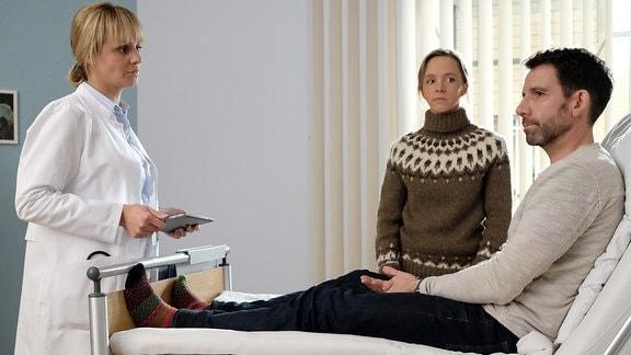 Dr. Lea Peters (Anja Nejarri, li.) erklärt Lutz und seiner Frau Nora (Johanna Klante, mi.), dass der bevorstehende Eingriff ein hohes Risiko birgt, umliegendes Gewebe zu verletzen und somit müssen die beiden mit kognitiven und motorischen Einschränkungen rechnen.