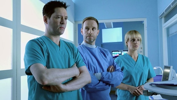 Dr. Kai Hoffmann (Julian Weigend, mi.) und Dr. Philipp Brentano (Thomas Koch, li.) bestätigen Leas Entscheidung und der Patient kannte die Risiken.