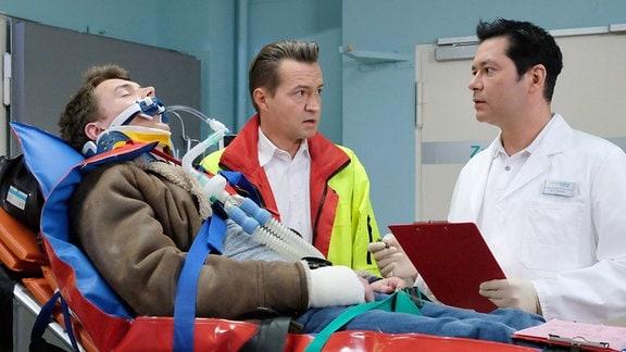 Kurz nach seiner Flucht mit dem Auto wird Malte Riedel (Gerrit Klein, li.) nach einem Autounfall vom Notarzt (Markus Neumann, mi.) wieder in die Sachsenklinik eingeliefert. Dort nimmt ihn Dr. Philipp Brentano (Thomas Koch, re.) entgegen der erst am Vortag Maltes Hand operiert hat.