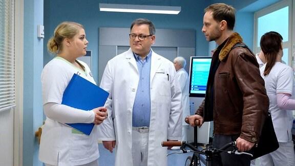 """Szene aus """"In aller Freundschaft"""": Drei Menschen stehen im Klinikflur und unterhalten sich."""