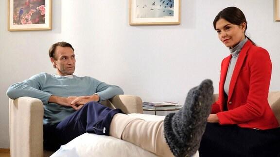 """Szene aus """"In aller Freundschaft"""": Ein Mann mit Gipsbein und eine Frau sitzen auf Sesseln."""