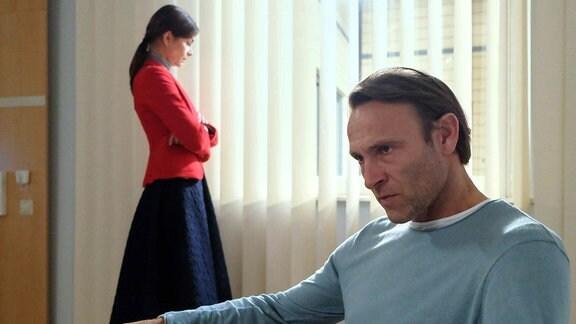 """Szene aus """"In aller Freundschaft"""": Ein Mann sitzt im Sessel, eine Frau steht etwas abseits am Fenster."""
