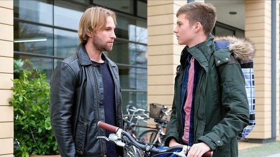 """Szene aus """"In aller Freundschaft"""": Zwei junge Männer unterhalten sich auf der Straße."""