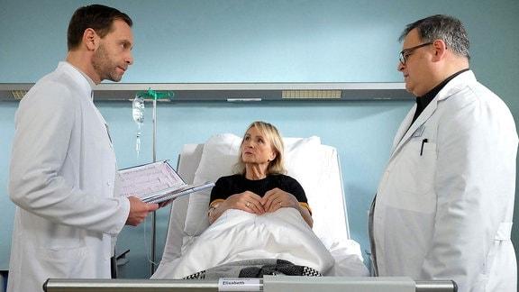 """Szene aus """"In aller Freundschaft"""": Zwei Ärzte bei einer Frau im Krankenbett"""