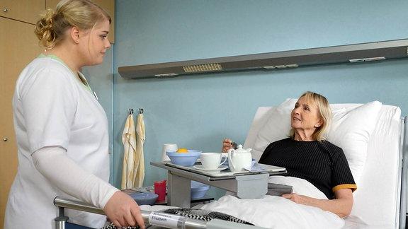 """Szene aus """"In aller Freundschaft"""": Eine Krankenschwester bei einer Frau im Krankenbett"""