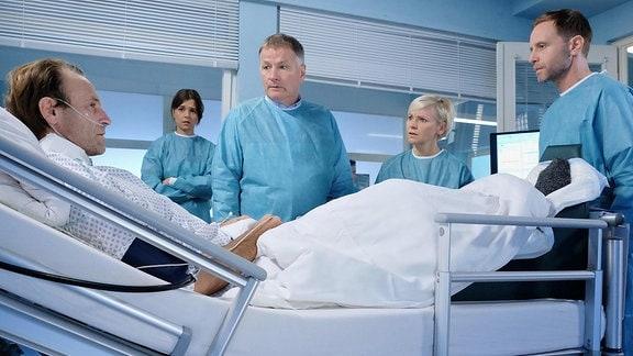 Dr. Martin Steins (Bernhard Bettermann, li.) Bein ist mit Gasbrand infiziert und es muss schnell gehandelt werden. Für Dr. Roland Heilmann (Thomas Rühmann, mi.) gibt es nur eine Möglichkeit seinem Freund das Leben zu retten: Amputation. Doch Dr. Kai Hoffmann (Julian Weigend, re.) schlägt eine weitere Operation und anschließend eine Sauerstofftherapie in einer Druckkammer vor. Dr. Kathrin Globisch (Andrea Kathrin Loewig, 2.v.re.) sagt Martin, dass die Zeit drängt. Er muss sich entscheiden: entweder die sichere Amputation oder die für sein Leben weitaus gefährlichere Möglichkeit Dr. Hoffmanns. Martins Freundin Sophia Müller (Susan Hoecke, 2.v.li.) hat Angst um Martin und will, dass er sich für die sichere Variante entscheidet.