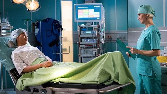 Marina Malik (Cynthia Micas, li.) ist Rheumapatientin und gibt die Einnahme von je einer Tablette pro Tag an. Dr. Kathrin Globisch (Andrea Kathrin Loewig, re.) wundert sich über die niedrige Dosierung.