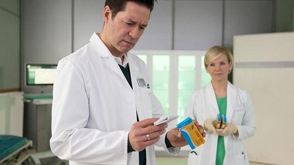 Dr. Brentano (Thomas Koch) blickt verständnislos auf das Medikament.