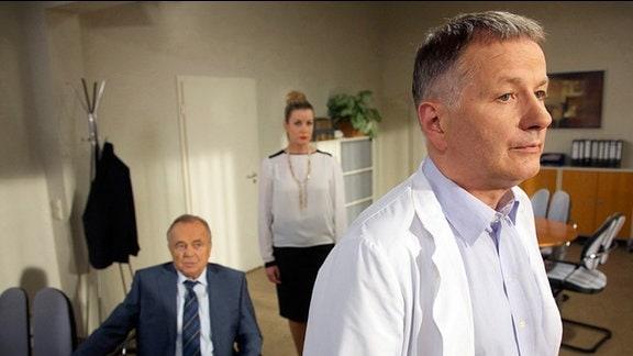 Thomas Rühmann als Dr. Roland Heilmann, Dieter Bellmann als Prof. Dr. Gernot Simoni und Alexa Maria Surholt als Verwaltungsdirektorin Sarah Marquardt