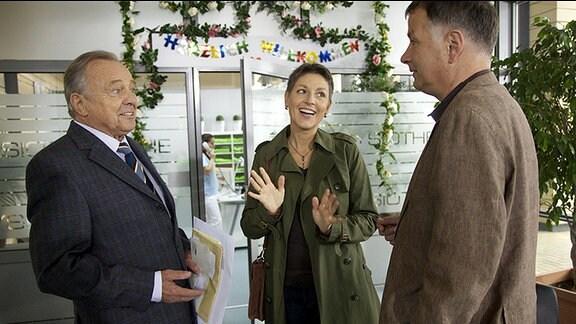 Pia Heilmann (Hendrikje Fitz, mi.) hat nach ihrer überstandenen Krebserkrankung ihren ersten Arbeitstag. Ihr Mann Roland (Thomas Rühmann, re.) möchte, dass sie es ruhig angeht. Professor Simoni (Dieter Bellmann, li.) heißt Pia im Namen der gesamten Belegschaft herzlich willkommen.