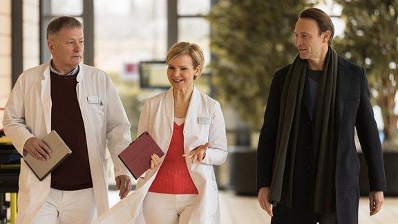 Roland Heilmann, Kathrin Globisch und Martin Stein laufen den Klinikgang entlang