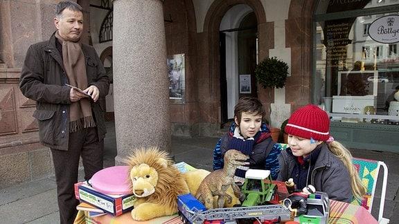 Pia Heilmann macht die Chemotherapie zu schaffen. Als kleine Aufmunterung wollen Lisa (Ella Zirzow, re.) und Jonas (Anthony Petrifke, mi.) sie mit einem Geschenk aufmuntern. Doch der Kassensturz zeigt, dass ihnen dazu das Geld fehlt. Kurzerhand schnappen sich die beiden ein paar ihrer Spielzeuge und wollen sie in der Stadt verkaufen. Doch das Geschäft läuft schleppend. Roland Heilmann (Thomas Rühmann, li.), wird auf seine beiden Kinder aufmerksam, ist ganz gerührt und versucht, den beiden unter die Arme zu greifen.