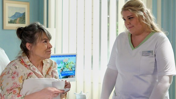 Schwester Miriam spricht mit Elfriede Machold im Patientenzimmer.
