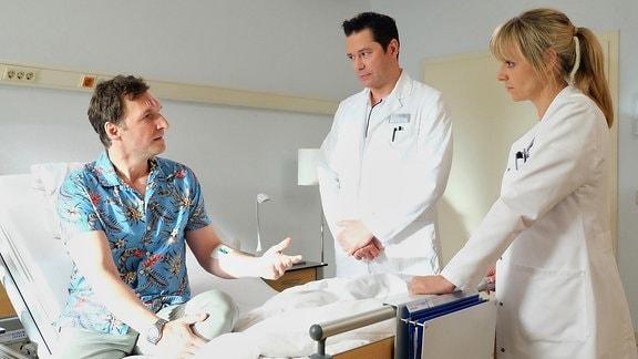 Dr. Lea Peters und Dr. Philipp Brentano mit Bob Herfort im Krankenzimmer.