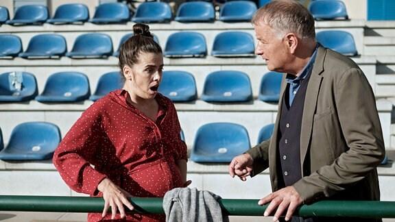 Roland Heilmann (Thomas Rühmann) mit der hochschwangeren Nadine Heller (Julia-Maria Kühler) auf dem Sportplatz.