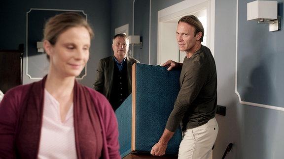 Martin Stein (Bernhard Bettermann, re.) trägt mit Roland Heilmann (Thomas Rühmann, mi.) ein Sofa. Katja Brückner (Julia Jäger, li.) ist dabei.