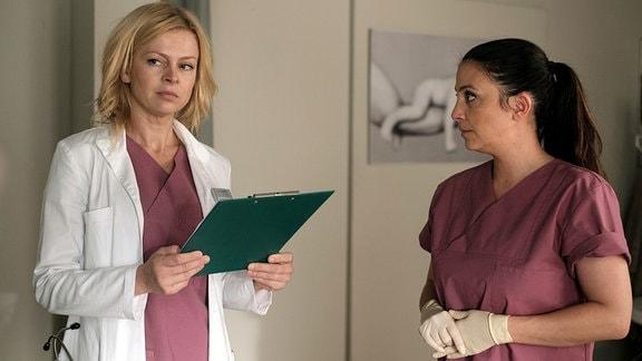Gynäkologin Dr. Ina Schulte (Isabell Gerschke, li.) und Oberschwester Arzu Ritter (Arzu Bazman, re.) betreuen eine Patientin, die über ihren Geburtstermin hinaus ist. In hält es nun für angebracht Nadine Heller an den Wehentropf zu hängen.