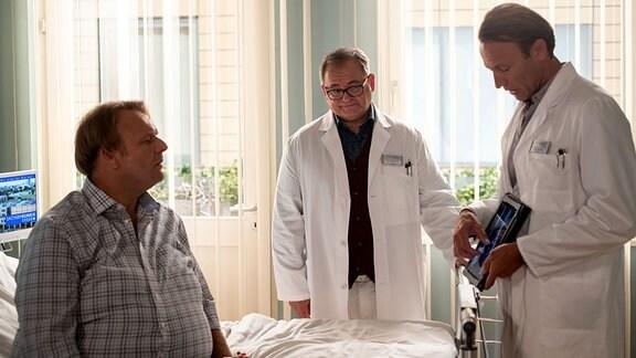 Quirin Härlein (Oliver Fleischer, li.) im Krankenzimmer mit Hans-Peter Brenner (Michael Trischan, mi.) und Dr. Martin Stein (Bernhard Bettermann, re.)