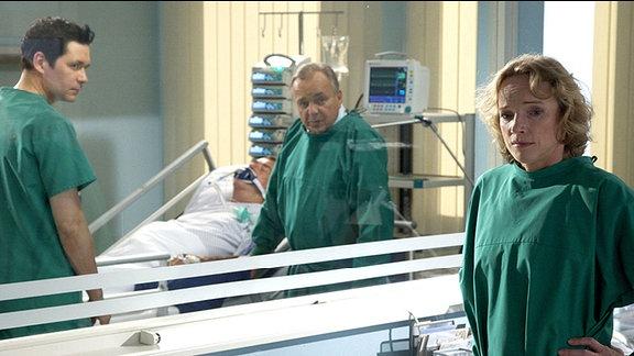 Horst Kramer (Wilfried Dziallas, liegend) hat einen weiteren Schlaganfall erlitten. Er muss dringend operiert werden, doch sein Zustand ist so kritisch, dass die Operation ein enormes Risiko birgt. Prof. Simoni (Dieter Bellmann, re.) und Dr. Philipp Brentano (Thomas Koch, li.) haben sich bei seiner Tochter Claudia (Claudia Geisler, vorn) nach einer Patientenverfügung erkundigt. Doch diese gibt es nicht. Claudia hat eine Vorsorgevollmacht - im Notfall liegt die Entscheidung ganz allein bei Claudia.