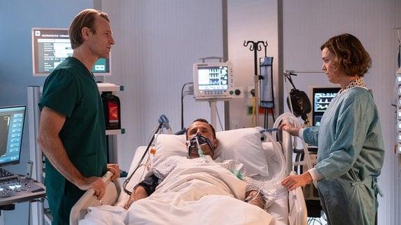 Auch Dr. Martin Stein (Bernhard Bettermann, li.) findet bei dem Mann (Stefan Timm, mi.) von Marianne Müller (Dominique Chiout) keine Ursache für seinen immer schlechter werdenden gesundheitlichen Zustand.