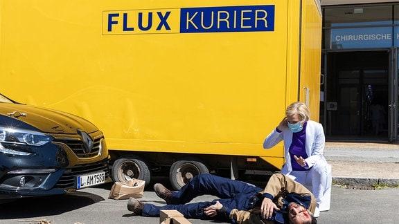 Dr. Kathrin Globisch  kniet auf dem Boden neben einem Kurierfahrer