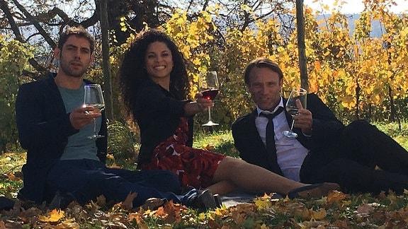 Drei Schauspieler im Herbstlaub mit Weinglaesern