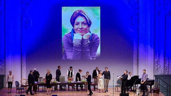Ein Bild von Hendrikje Fitz wird eingeblendet, davor das Ensemble von In aller Freundschaft auf der Bühne