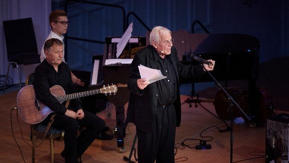Rolf Becker auf der Bühne und Thomas Rühmann im Hintergrund an der Gitarre