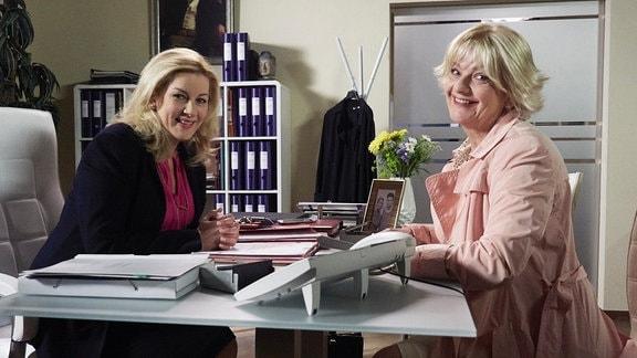 Zwei Schauspielerinnen am Tisch lachen in die Kamera