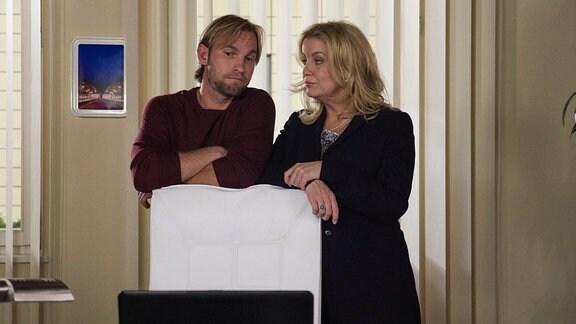 Ein Mann und eine Frau lehnen an einem Stuhl und blicken einander in die Augen