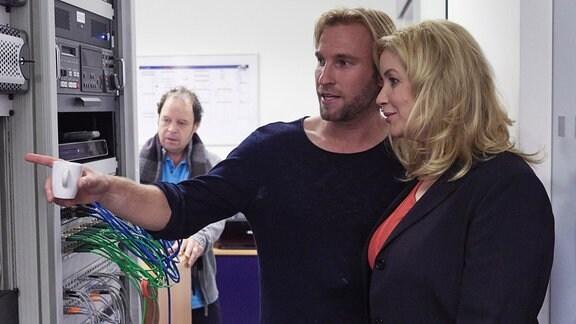 Ein Mann und eine Frau betrachten Computerkabel