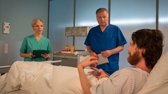 Dr. Kathrin Globisch und Dr. Roland Heilmann stehen am Bett des Patienten.