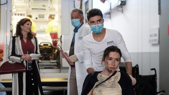 Sandy Winter (Christin Alexandrow, re.) wird in die Sachsenklinik eingeliefert. Dr. Roland Heilmann (Thomas Rühmann, 3.v.re.) bittet Pfleger Kris Haas (Jascha Rust, 2.v.re.), sie in den Behandlungsraum zu bringen.