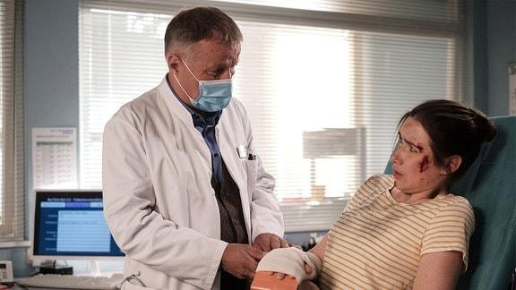 Sandy Winter (Christin Alexandrow) erzählt Dr. Roland Heilmann (Thomas Rühmann), dass Vera Bader sie zu Boden gestoßen hat.