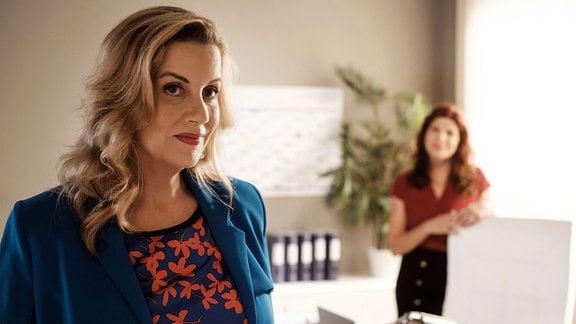 Sarah Marquardt (Alexa Maria Surholt, li.) hat sich trotz ihres vollen Schreibtisches bereit erklärt, für eine Stunde die Aufsicht für Vera Bader (Claudia Wenzel, re.) zu übernehmen.