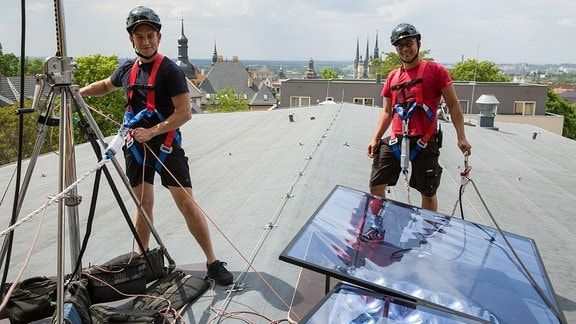 Zwei Männer in Sicherheitsgurten arbeiten auf einem Dach