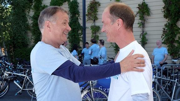 Holger Daemgen und Thomas Rühmann begrüßen sich am Set und freuen sich.
