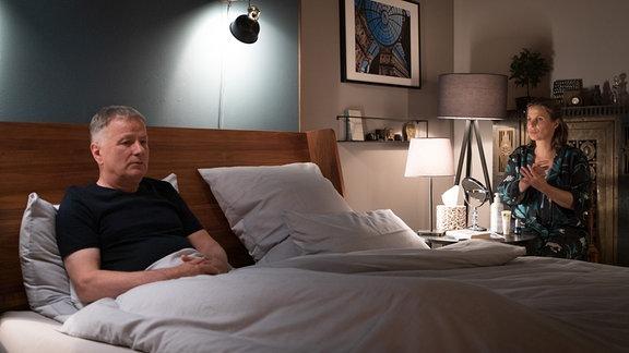 Katja Brückner (Julia Jäger) erzählt Dr. Roland Heilmann (Thomas Rühmann) etwas im Bett.