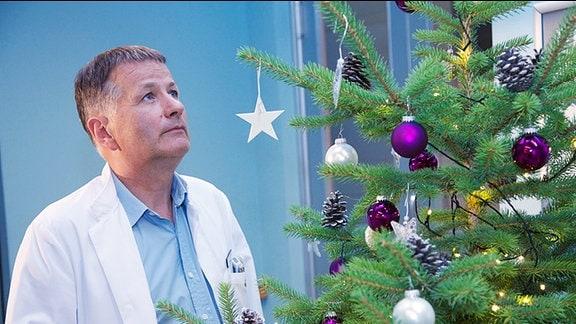 Thomas Rühmann (Dr. Roland Heilmann) vor dem Weihnachtsbaum